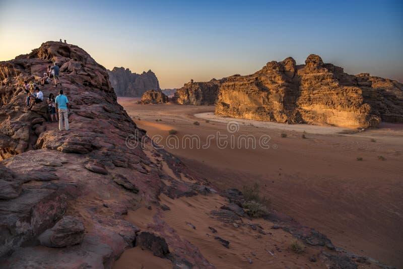 Desierto Jordania, 17-09-2017 de Wadi Rum Un grupo de personas sube en una montaña para considerar el sol poniente mejor imagenes de archivo