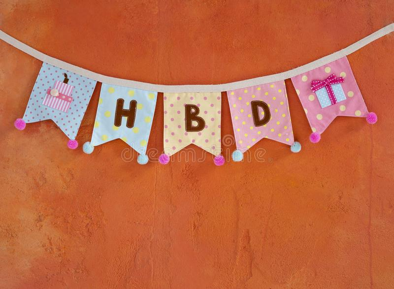 Design Birthday party flag hanging on orange cement wall. Texture background stock photography