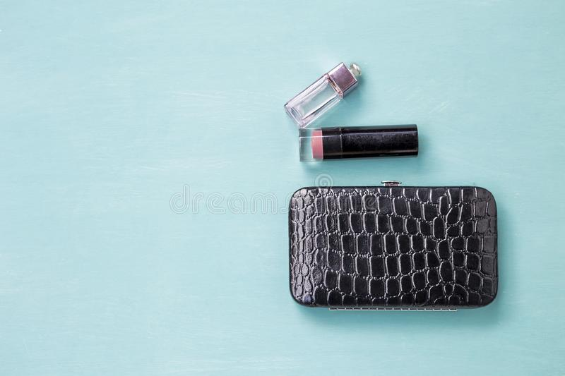 Design black shiny leather purse with lipstick stick and a bottle of perfume. On blue wood texture background royalty free stock photography