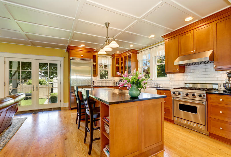 Design of brown wooden kitchen with steel appliances. Bar style kitchen island with fresh flowers and pendant lights. Northwest, USA royalty free stock photos