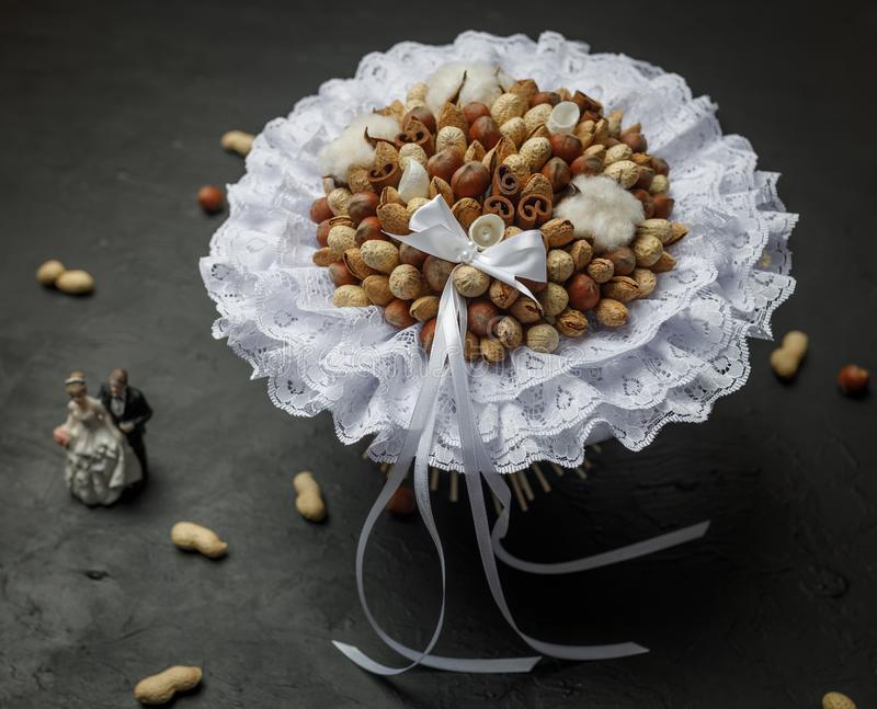 Design composition in the form of an original wedding bouquet from nuts on a black background.  stock photo