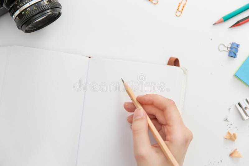A girl is holding a pencil in her hand and preparing to write in a notebook.  on white background. Top view. stock image