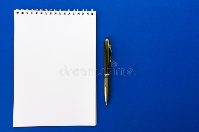 Top view of a spiral school notebook and pens collection on a blue background for layout. Design concept - Top view of a spiral school notebook and pens royalty free stock photography