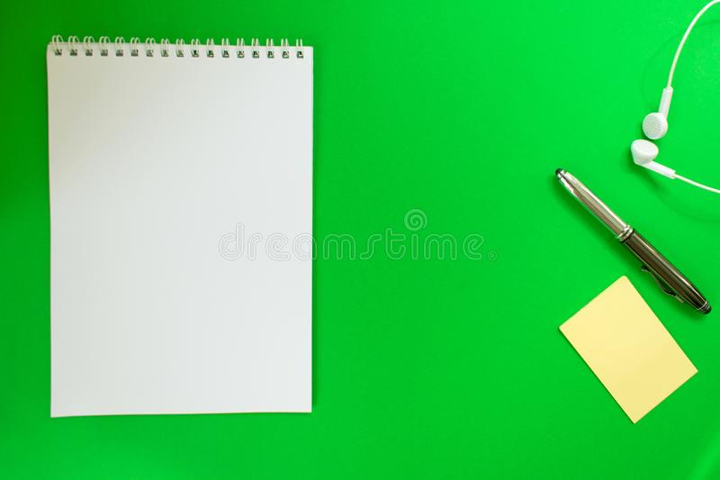 Top view of a spiral school notebook, pens and headphones collection on green background for mockup. Design concept - Top view of a spiral school notebook, pens royalty free stock photography