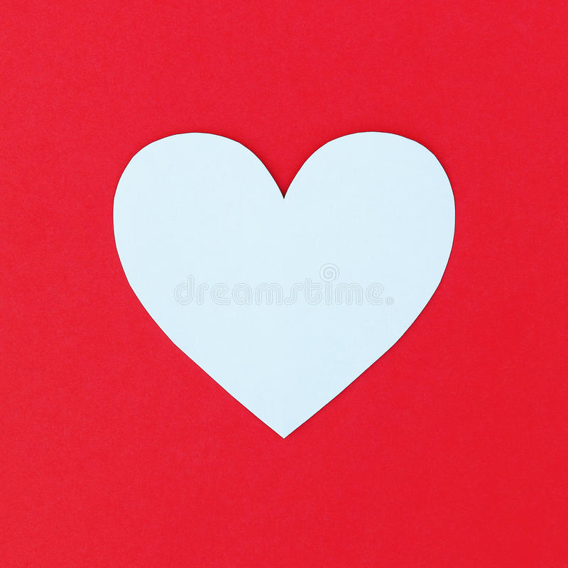 design of cutting white paper heart on red paper background stock image