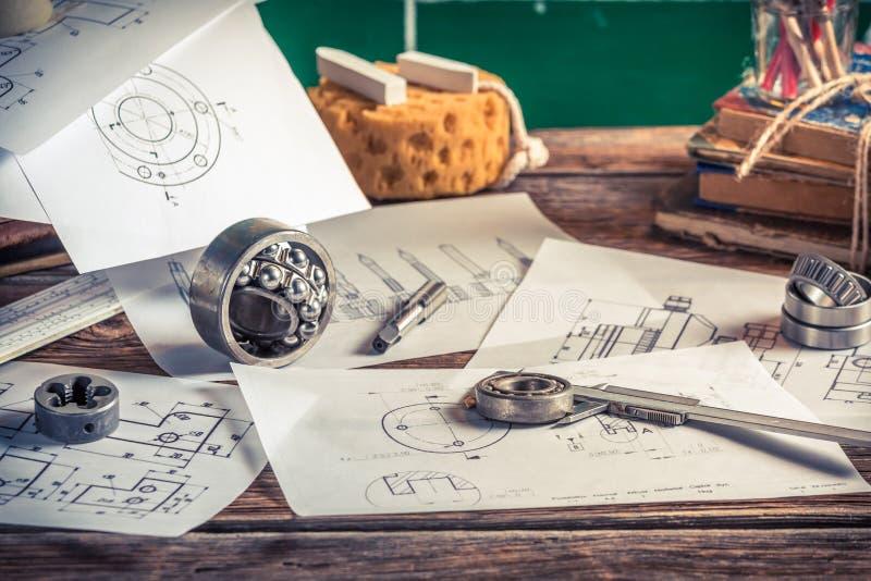 Design, das mechanische Teil in der Werkstatt zeichnend und messen stockbilder