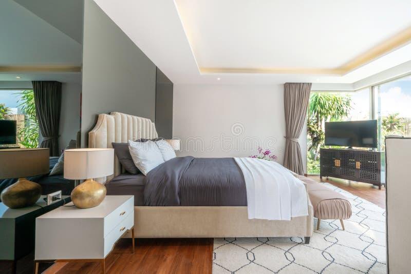 Design de interiores luxuoso dos bens imobili?rios no quarto da casa de campo da associa??o com a cama acolhedor do rei imagens de stock