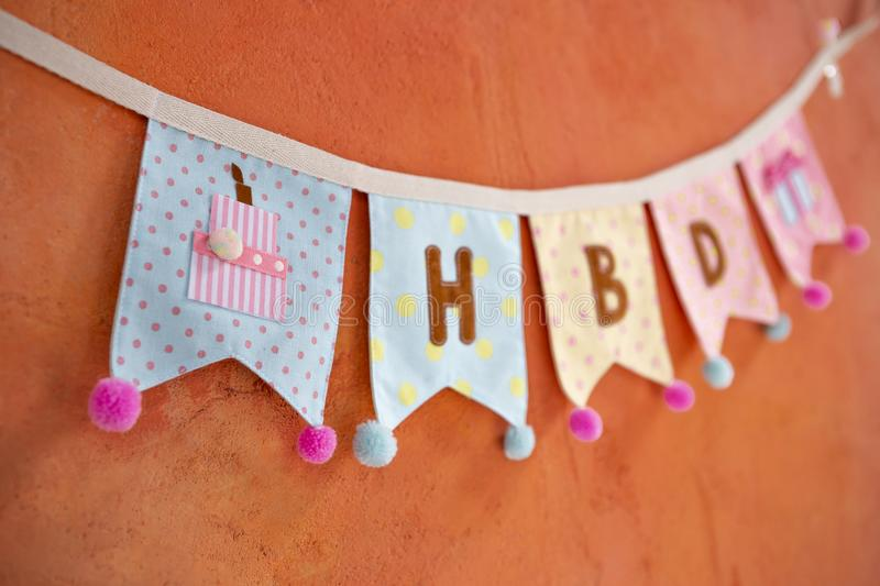 Design fabric birthday party flag hanging on orange cement wall. Background royalty free stock image