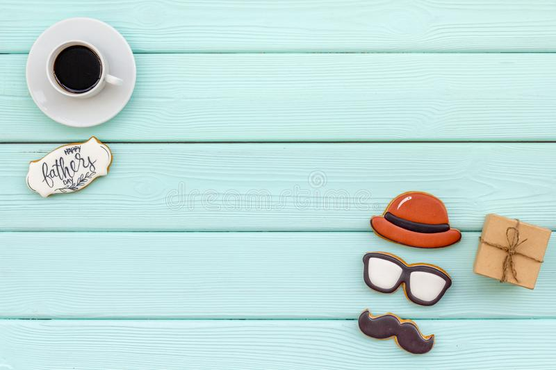 Design for Father Day celebration party with cookies, gift box and coffee on mint green background top view mock up. Hat, moustache, glasses figures. Design for stock image