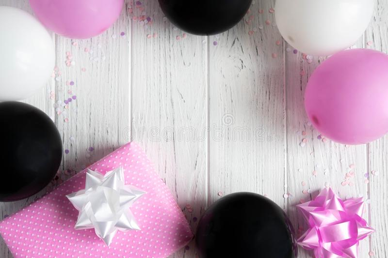 Design frame for birthday card background. Pink, white and black balloons with a gift box on a light wooden background.  royalty free stock image