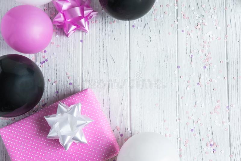 Design frame for birthday card background. Pink, white and black balloons with a gift box on a light wooden background. Greeting. Design frame for birthday card royalty free stock photo