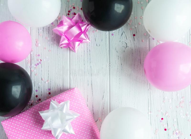 Design frame for birthday card background. Pink, white and black balloons with a gift box on a light wooden background. Greeting. Design frame for birthday card stock photos