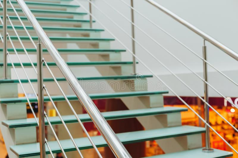 Design glass ladder with metal hand-rail in the trading floor of. VOLGOGRAD, RUSSIA - 19 December, 2018: A design glass ladder with metal brilliant hand-rail in royalty free stock photos