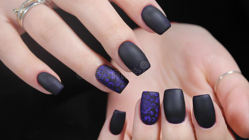 Design of manicure matt black and blue nails. Design of manicure nails matt black and blue nails stock photography