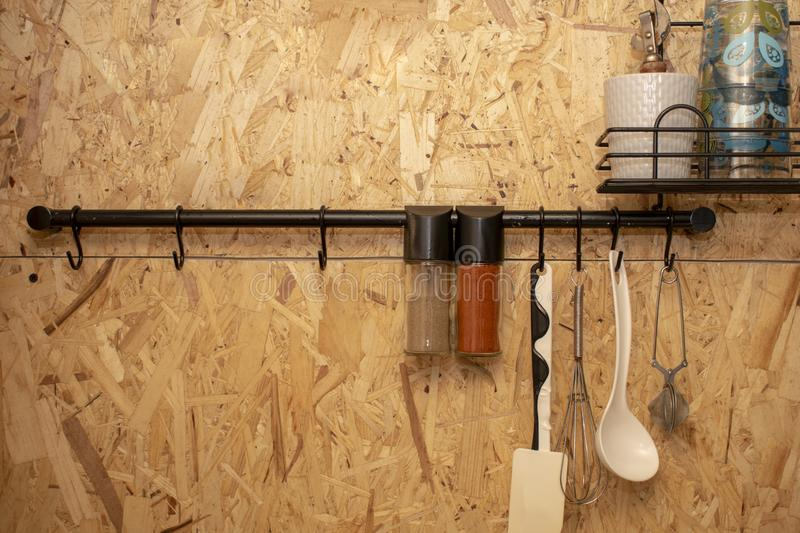 The design of the modern home kitchen in the loft-style and rustic. Wooden wall with kitchen utensils, spice and glasses royalty free stock photo