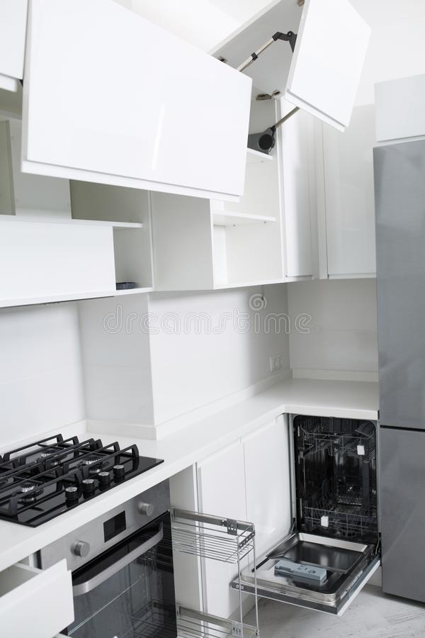 Design of a new light kitchen in pastel colors. There is a dishwasher in the kitchen stock photography
