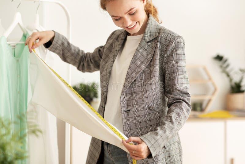 Design personale Dressmaker che misura la lunghezza del manicotto in un atelier immagini stock