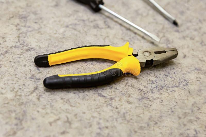 Design web borrado da decoração do projeto industrial do fundo da peça do close-up dos alicates da ferramenta chave de fenda amar imagem de stock