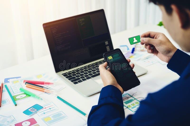 Design web novo de trabalho do teste do programador no portátil do computador com telefone celular no escritório Conceito de prog imagens de stock