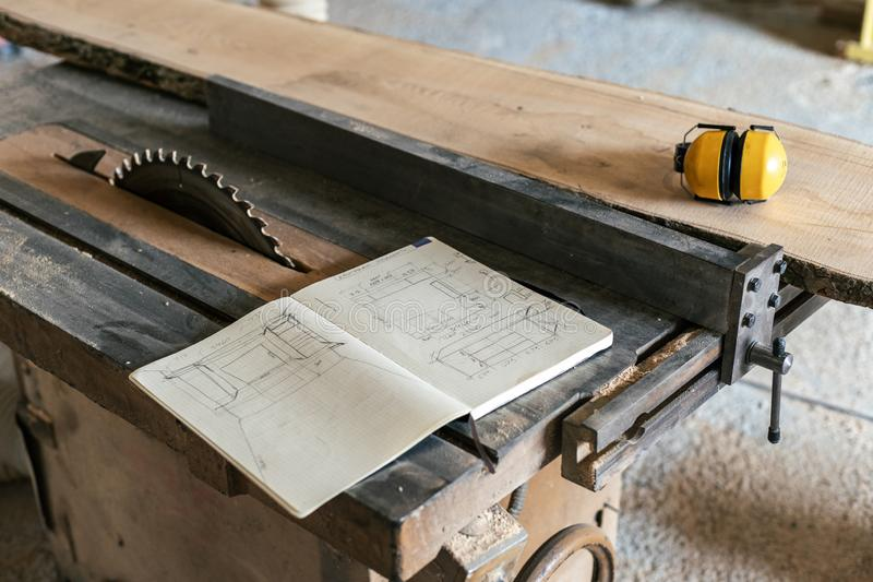 Design wood small business concept. Technical drawing in notebook lying on top of wood in garage or workroom near yellow headset. And table saw royalty free stock image