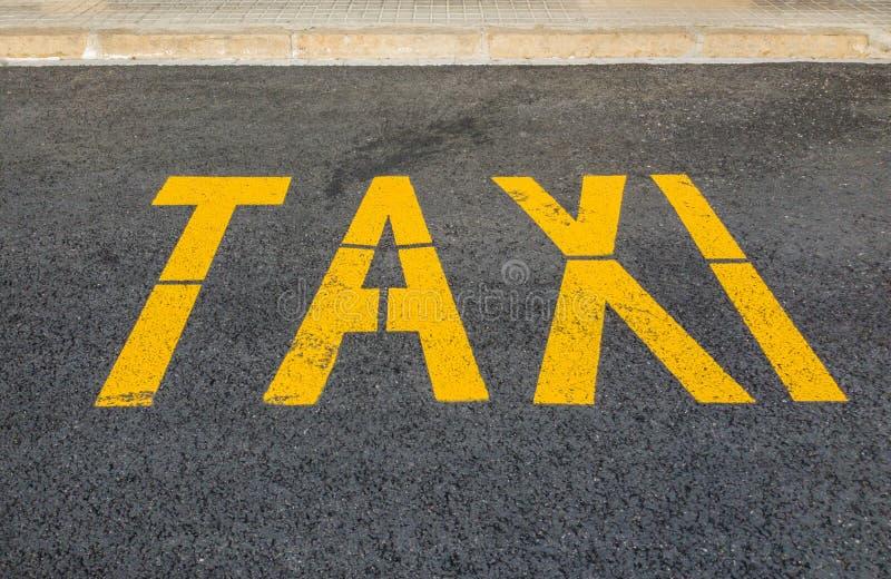 Designación de la fila de taxi en el asfalto amarillo de la pintura imagenes de archivo