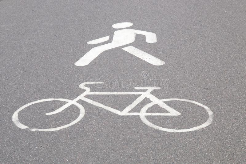 Designation of a bicycle path and pedestrian walkway painted on asphalt stock image