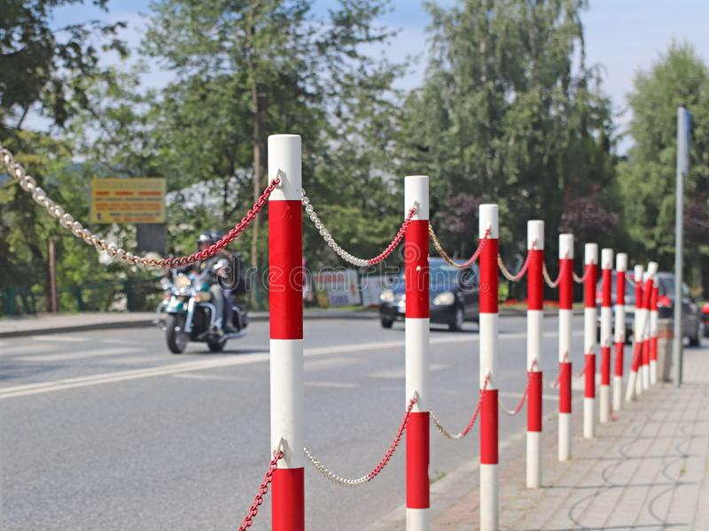 The designation of traffic signs for the separation of pedestrian and transport zones for traffic safety. Red and white markings. Handrail with chain. Traffic stock photo