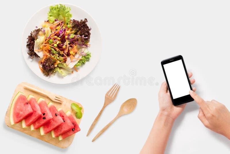 Designbegrepp av modellen genom att använda smartphonen med sallad, vattenmelonuppsättning royaltyfri foto