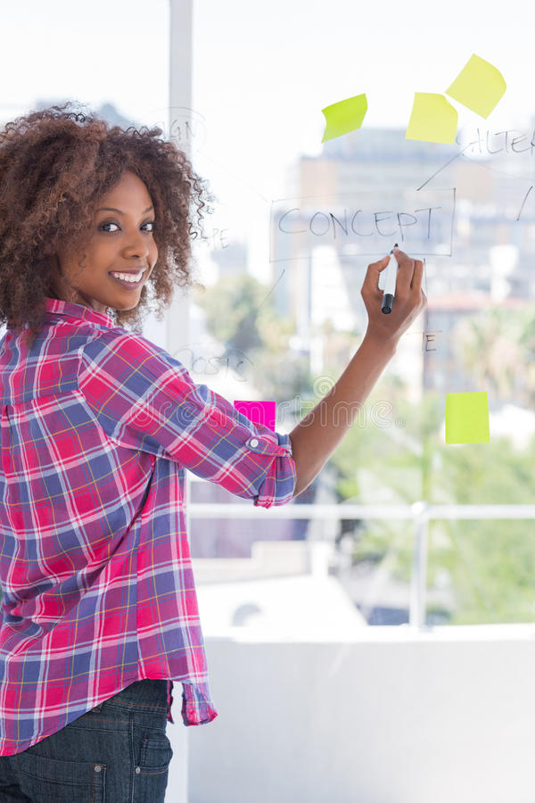 Designer adding to flowchart on window. And smiling at camera royalty free stock images