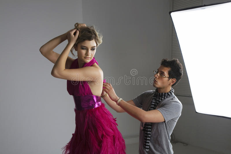 Designer adjusting dress back of fashion model in studio stock photography