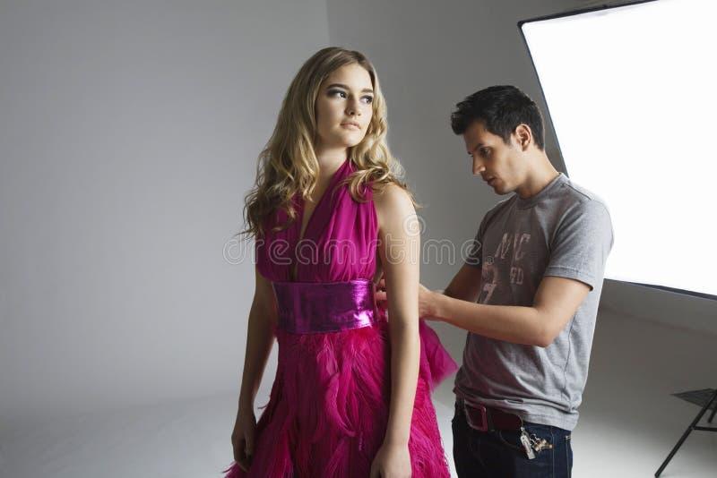 Designer adjusting dress back on fashion model in studio royalty free stock images