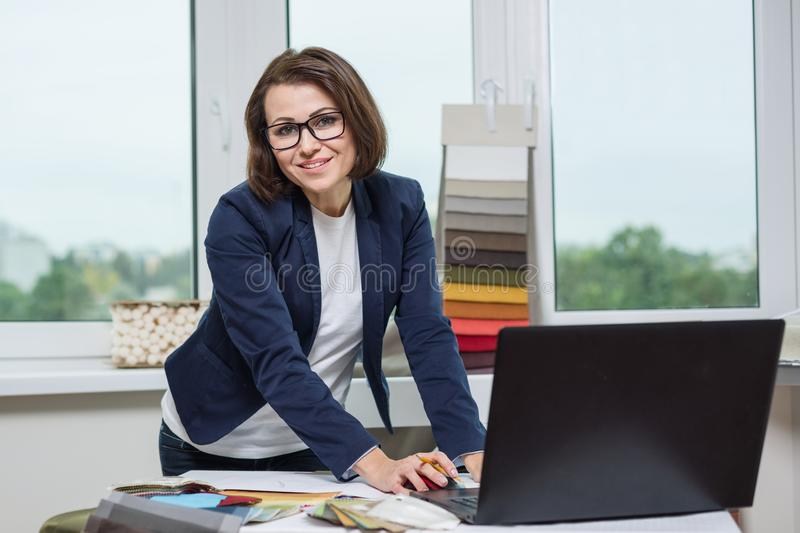 Designer or architect posing and looking at you works with samples of fabrics for curtains and blinds, background office window. stock image