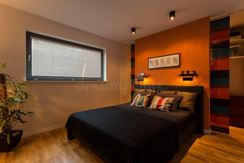 Designer bedroom with orange wall royalty free stock photo