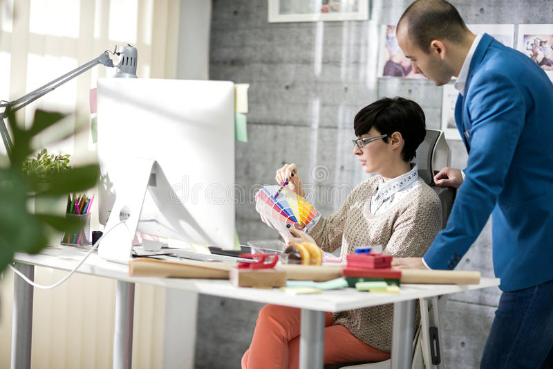 Designer with colleague at design studio. Female designer with male colleagues at design studio royalty free stock image