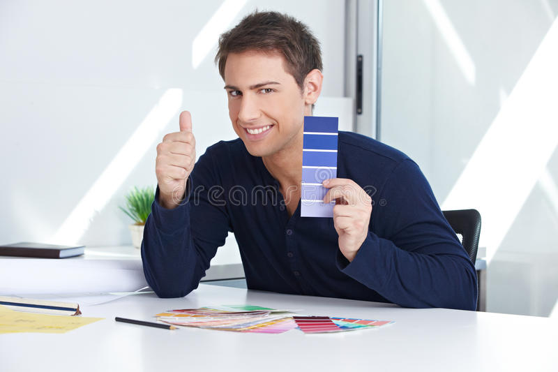 Designer with color samples holding. Designer with blue color samples at his desk in the office holding thumbs up royalty free stock photography
