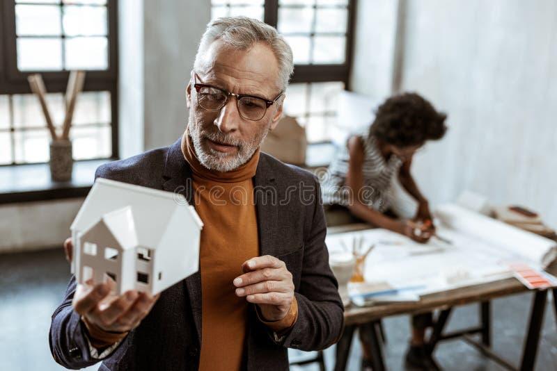 Designer de interiores cinzento-de cabelo farpado que guarda o modelo branco da casa foto de stock