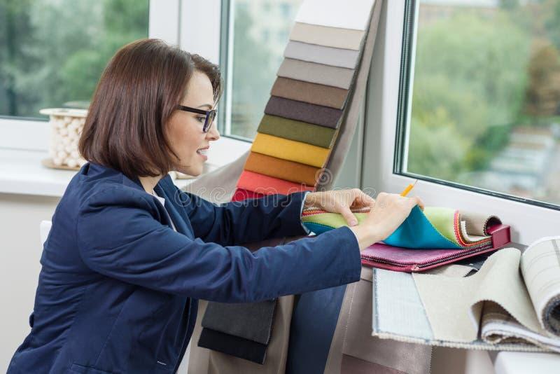 Designer de interiores da mulher, trabalhos com as amostras de telas para cortinas e cortinas fotos de stock royalty free