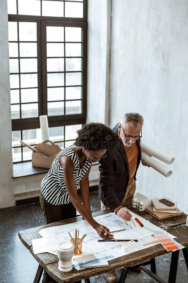 Designer de interiores que dá algumas ordens a seu estagiário útil imagens de stock