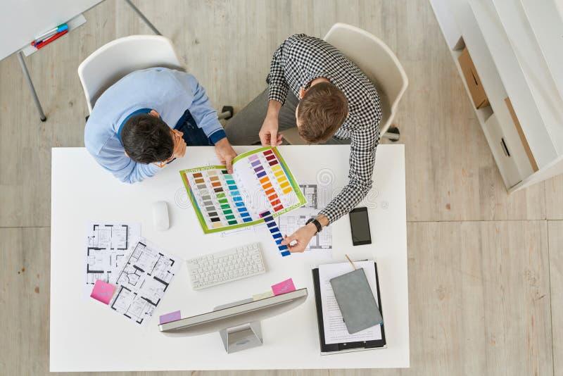 Designer de interiores que discutem planos da casa imagem de stock