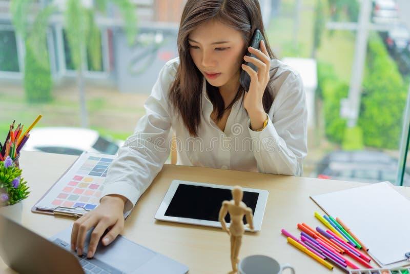 Designer der jungen Frau, der mit Tablettenfarbproben für Auswahl auf Schreibtisch arbeitet, lizenzfreies stockfoto