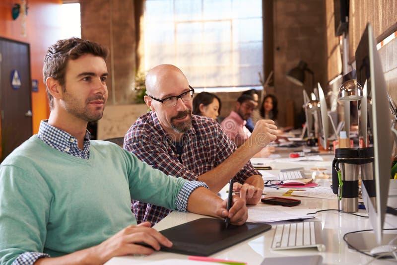 Designer, die an den Schreibtischen im modernen Büro zusammenarbeiten lizenzfreie stockbilder