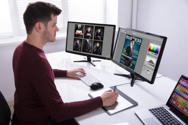 Designer Drawing On Graphic Tablet While Working On Computer stock photos