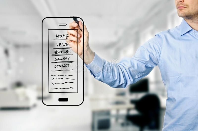 Designer drawing mobile website development wireframe. Blurred office in background stock photography