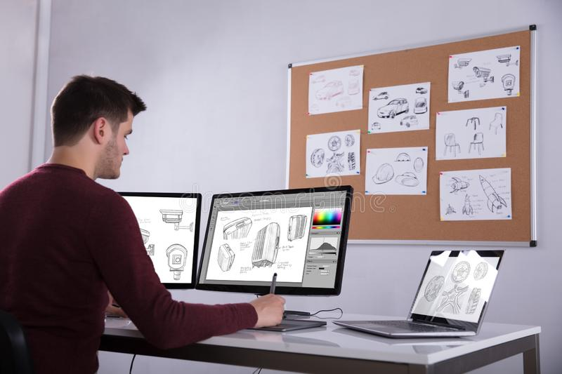 Designer Drawing Suitcase On Computer Using Graphic Tablet. E View Of Designer Drawing Suitcase On Computer Using Graphic Tablet In Office royalty free stock image
