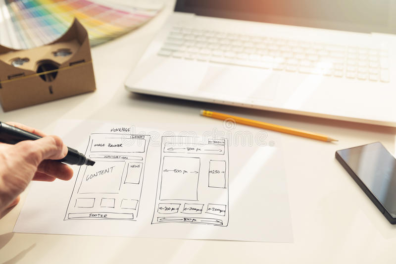 Designer drawing website development wireframe on paper. In office royalty free stock photo