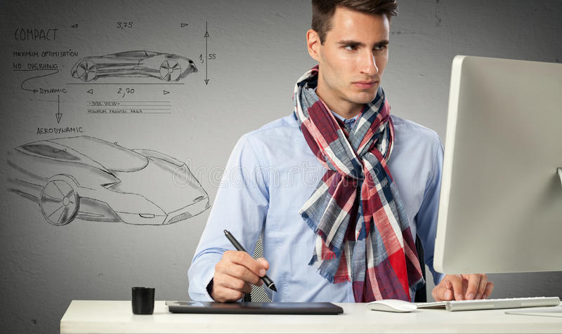 Designer draws a model car. Designer sitting front of computer and draws a model car stock photography