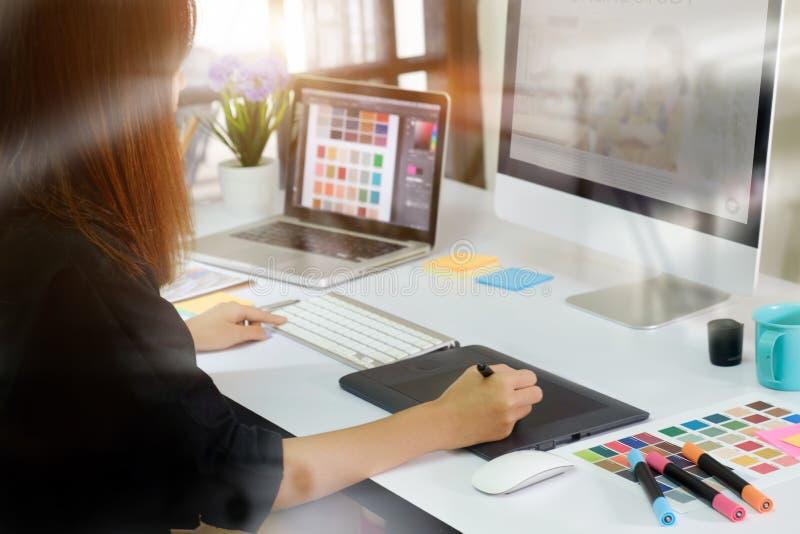 Designer gráfico asiático novo que trabalha no computador foto de stock