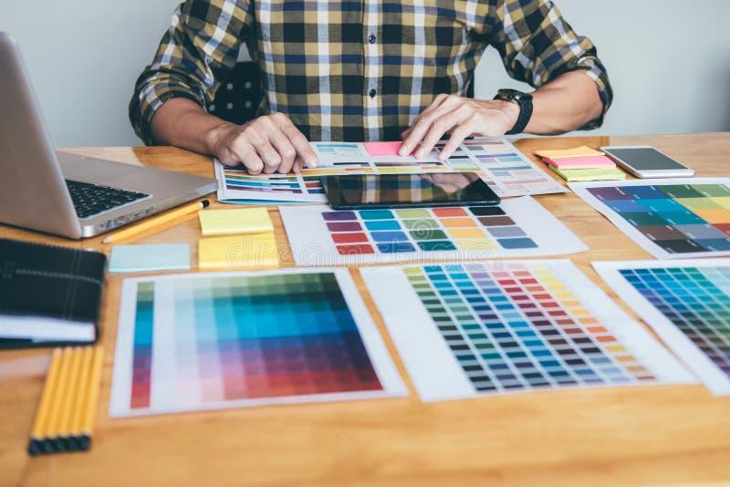 Designer gráfico criativo novo que usa a tabuleta de gráficos ao choosin fotos de stock