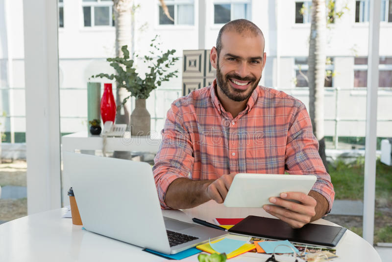 Designer gráfico de sorriso que usa a tabuleta na mesa no escritório foto de stock royalty free