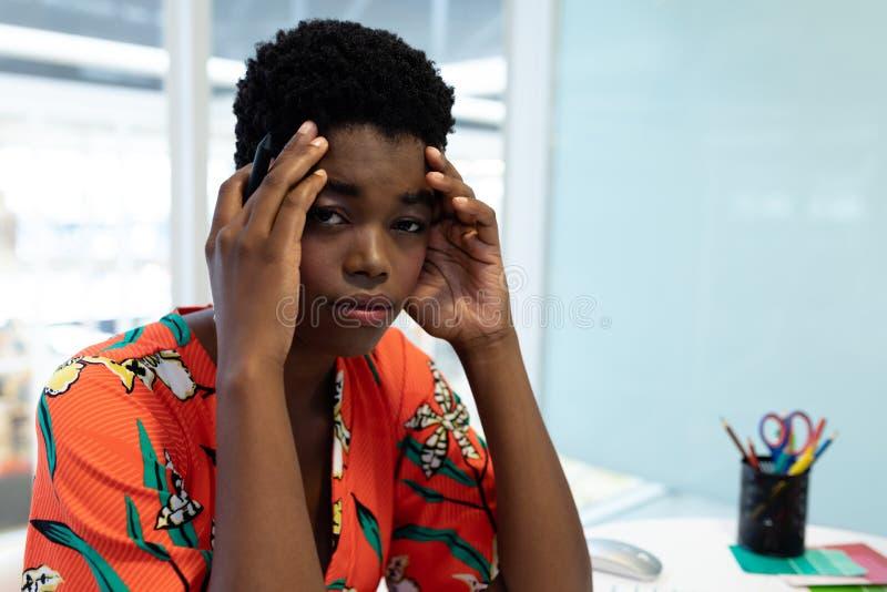 Designer gráfico fêmea forçado que senta-se na mesa fotografia de stock